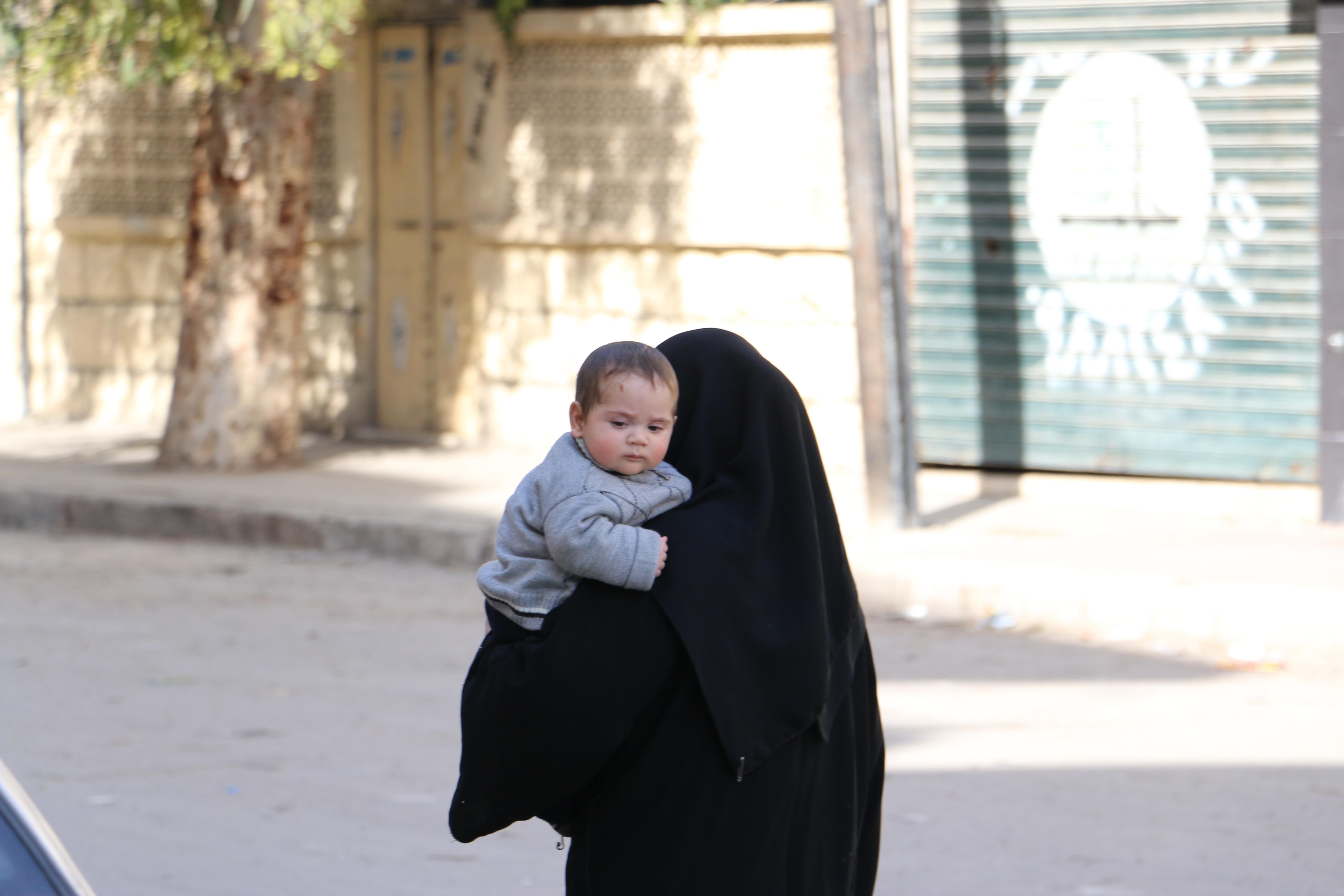 أمرأة-تحمل-رضيعها-وتمشي-في-حي-الزبدية-