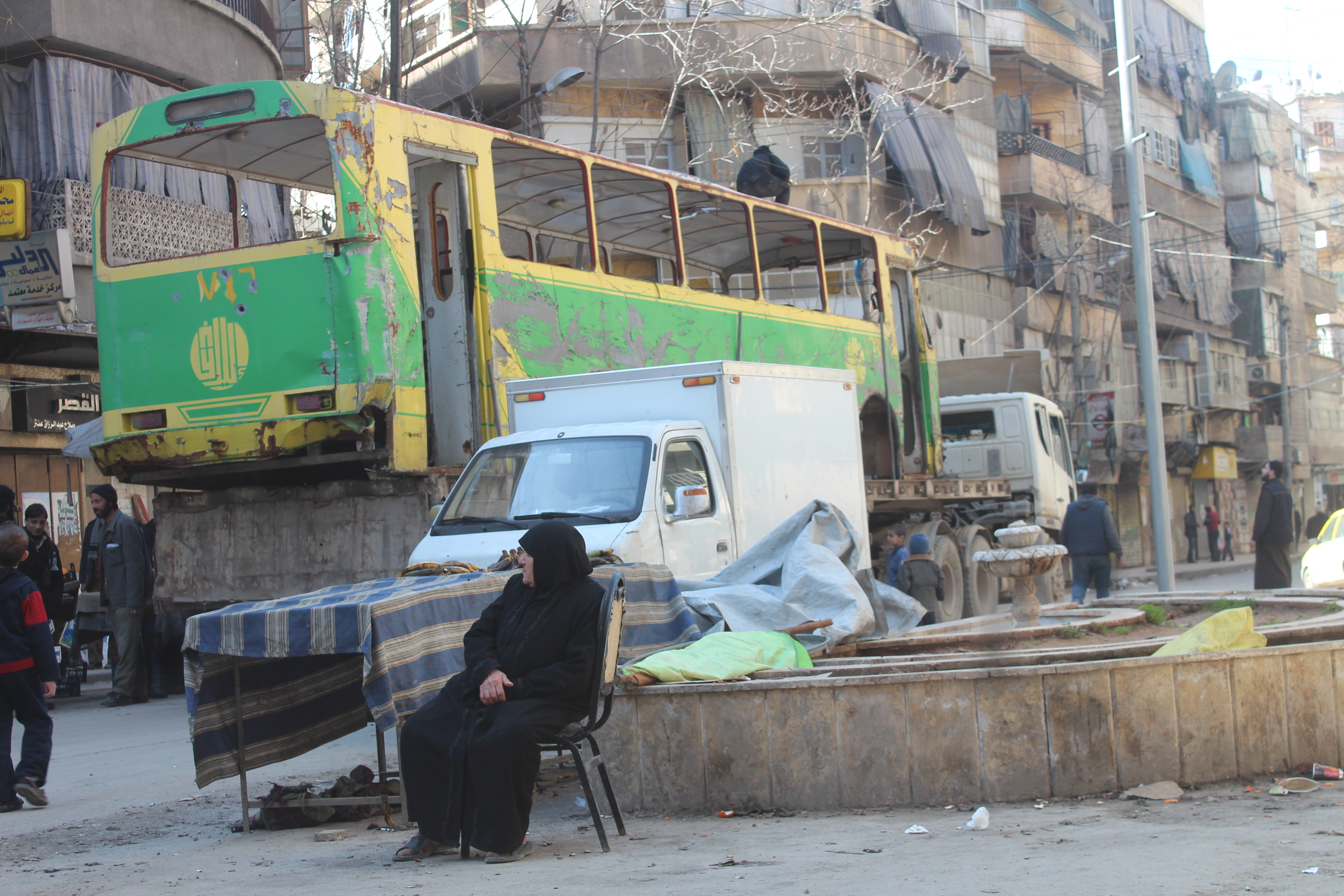 An elderly woman rests in the Aleppo neighbourhood of Kallaseh before continuing on her way home.