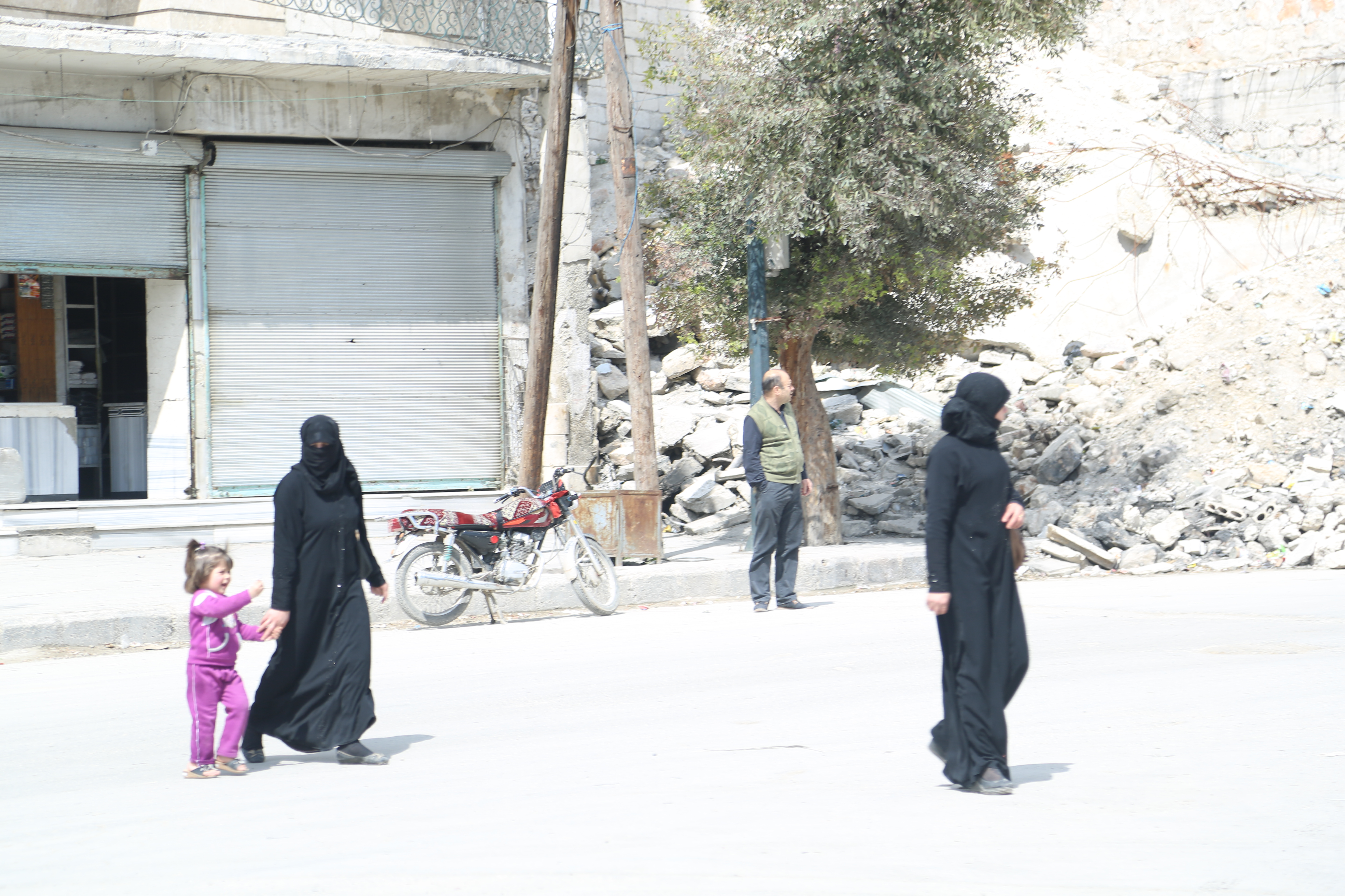 A woman and her daughter cross the street in front of a destroyed building in the al- Marja neighbourhood. Photo by: Hussam Kuwaifatiyeh