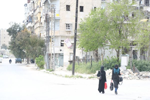 Two women walk through the al-Shaar neighbourhood. Photo by : Hussam Kuwaifatieh