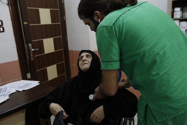 An elderly woman is examined at the internal medicine clinic of the al-Quds hospital in Aleppo. Photo: Mujahid Abu al-Jud.