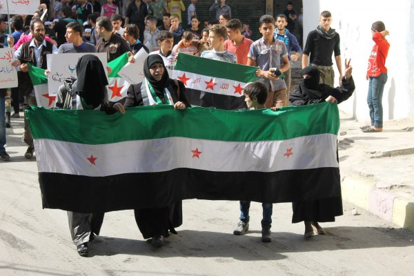 Women take part in a demonstration calling on Syrian factions to unite. Photo by: Mujahid Abu al-Joud