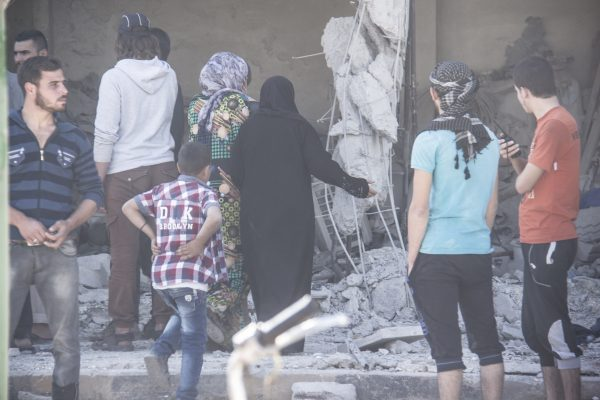 Women inspect a home targeted by the regime. Photo: IWPR
