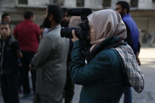 A journalist takes pictures of an Aleppo demonstration calling on the Free Syrian Army to break the siege of the city. Photo: Mujahid Abu al-Joud
