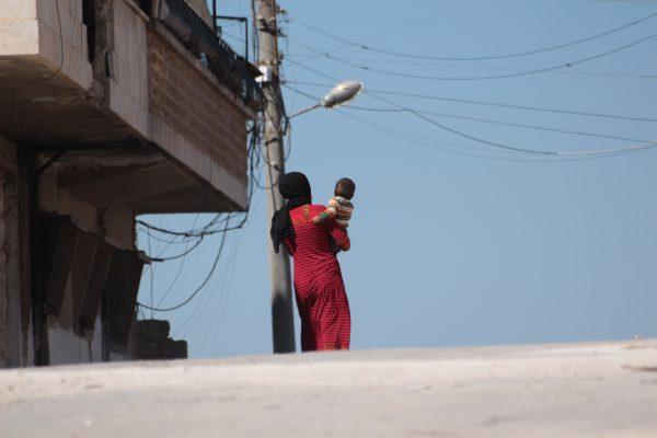 إمرأة في ريف إدلب تحمل طفلها