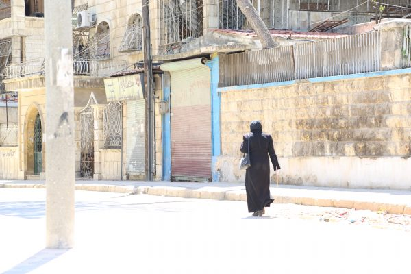 A woman walking through the Saif al-Dawla neighbourhood. Photo: Hussam Kuwaifatiah