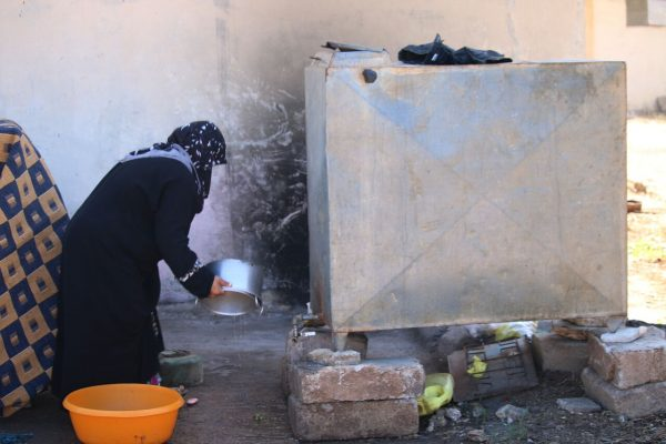 امرأة سورية تقوم بجلي الأواني المنزلية في أحد أحياء مدينة درعا في جنوب سوريا.