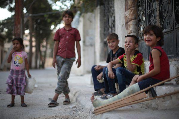 طفل متصاوب بقدمه من اثر القصف يجلس في الطريق مع اصدقائه
