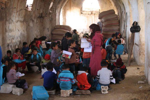 انسة سورية تعطي درساً لاطفال نازحين في مدرسة أقيمت بشكل مؤقت في بلدة المسيفرة بريف درعا الشرقي.