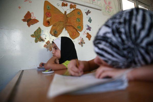 """أطفال يحضرون دورة صيفية في أحد مدارس مدينة دوما، الدورة تتضمن """"مواد تعليم مسرع"""" للأطفال الذين انقطعوا عن الدراسة في السنوات الماضية بسبب ظروف الحرب في سوريا. الصورة بتاريخ 16-08-2017."""