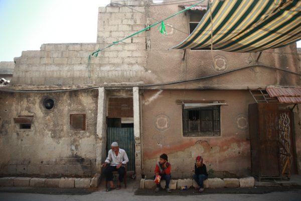 رجل كبير في السن يجلس في أحد أحياء مدينة زملكا التي تعرضت للقصف المباشر بالصواريخ الكيماوية في عام2013. الصورة بتاريخ 20-08-2017.