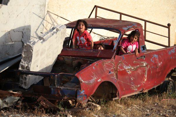 : طفلات سوريات يلعبن داخل سيارة مدمرة في أحد أحياء مدينة درعا جنوب سوريا