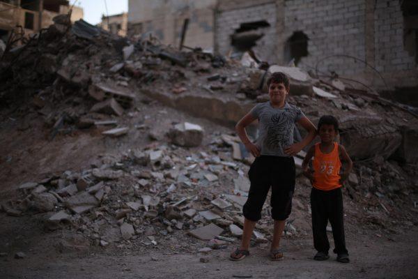 اطفال من مدينة زملكا ورائهم بناء مدمر