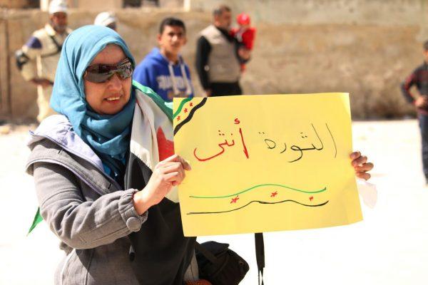شابة سورية تشارك في إحدى المظاهرات المناهضة للنظام السوري وتحمل لافتة في مدينة درعا جنوب سوريا