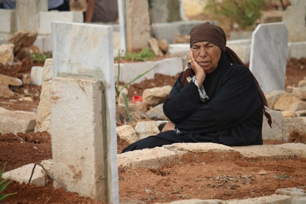 امرأة سورية تجلس بالقرب من أبنها الذي قتل بقصف لقوات النظام على أحياء مدينة درعا.