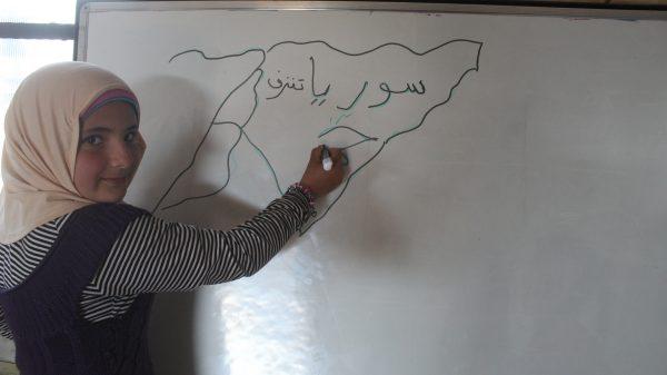 . طفلة سورية في احدة مدارس المخيمات، ترسم خريطة سوريا، الوطن الذي تحلم ان تعيش فيه امنة