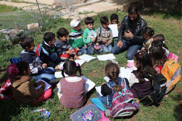 أستاذ سوري يجلس مع الأطفال على العشب أثناء أعطائه درس في الرسم بأحد روضات الأطفال في مدينة درعا جنوب سوريا.