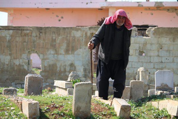 رجل مسن سوري يمشي بالقرب من القبور في أحد أحياء مدينة درعا جنوب سوريا