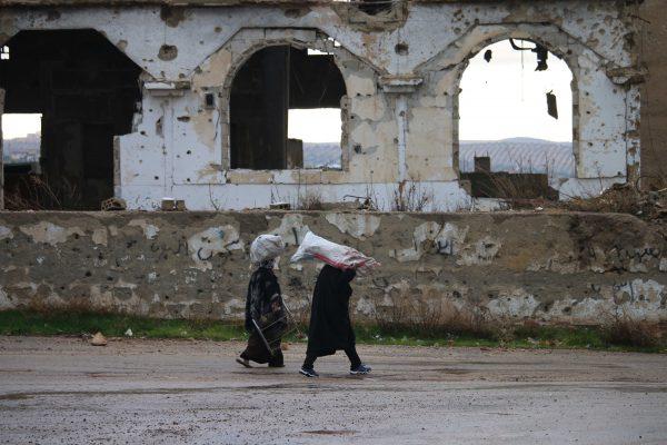 رجل وإمرآة سورية يحملون أكياس على أكتافهم في أحد أحياء مدينة درعا جنوب سوريا.