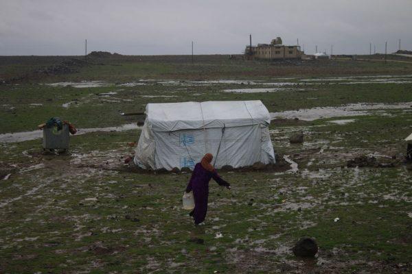 امرأة سورية تحمل كالون من الماء في مخيم الرفيد بريف محافظة القنيطرة.