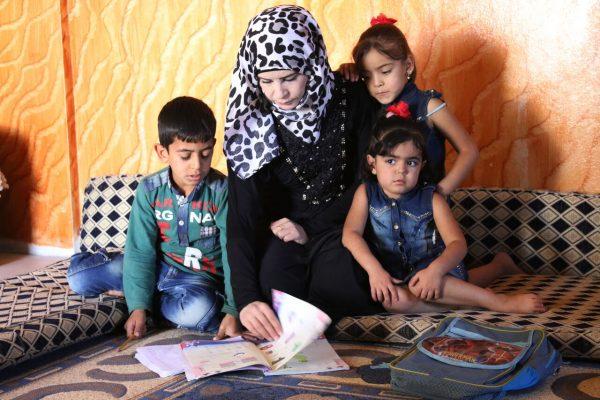 أم سورية تعلم أطفالها القراءة والكتابة في أحد أحياء مدينة درعا في جنوب سوريا.